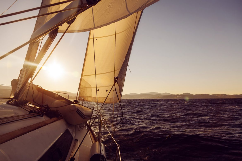 Sailboat crop during the regatta at sunset ocean.